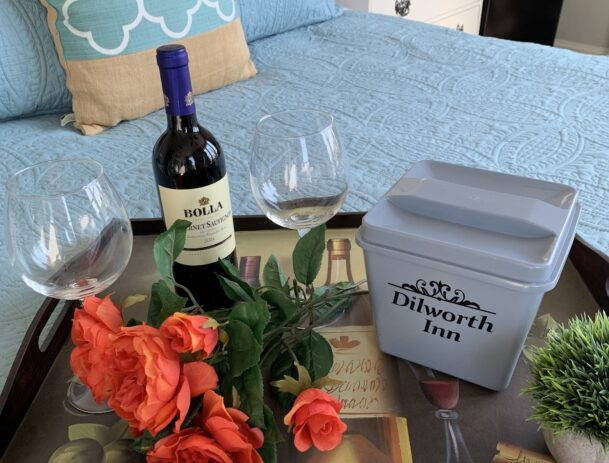 A tray holds two glasses and a bottle of wine plus fresh cut roses resting on a plush and colorful bed.
